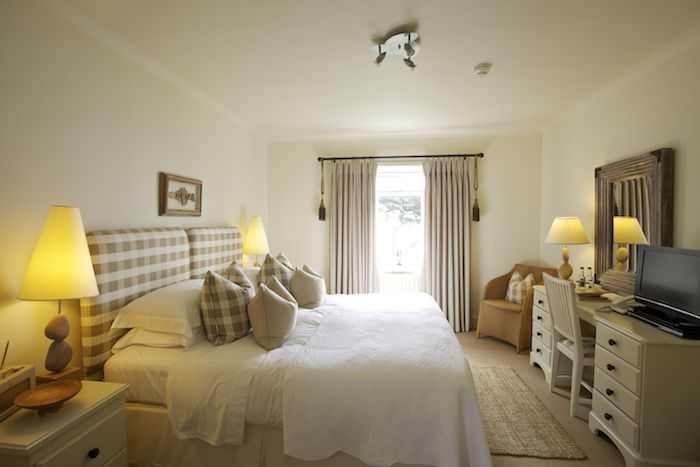 A bedroom at luxury hotel in Cornwall, the Driftwood, with a huge double bed and patio doors leading to a balcony and view of the sea.