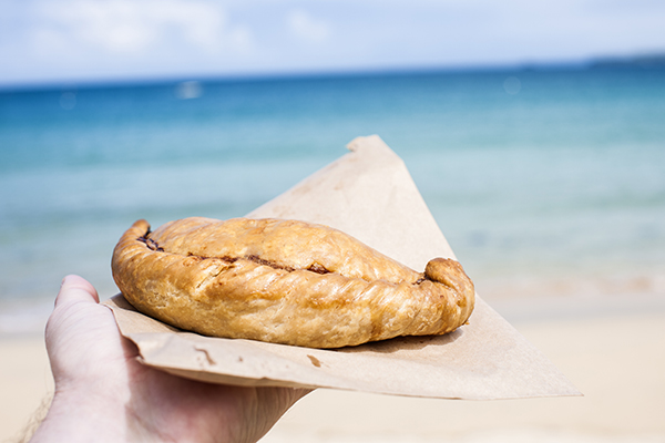 A Cornish pasty on a paper bag held out by a hand with the sea and beach in the background.