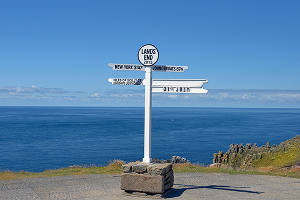The sign at Lands End showing the distances to far off land marks, with the sea in the background and no other land in sight.