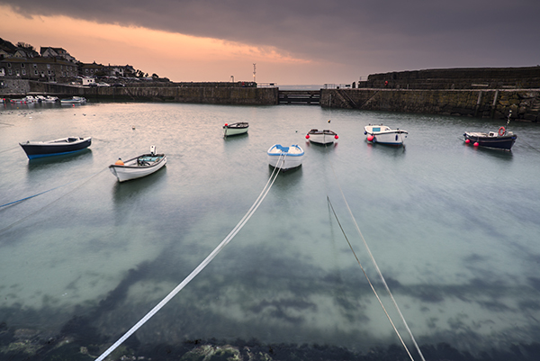 The harbour at St Ives with boats tied to the walls around and floating on clear, clean water.
